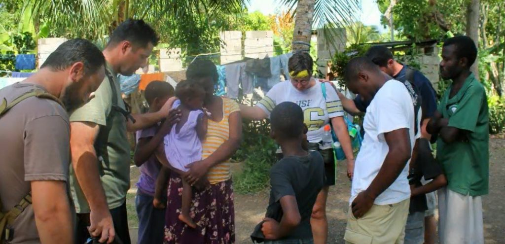 Missionaries praying with Haitian citizens after a successful day of mission work.