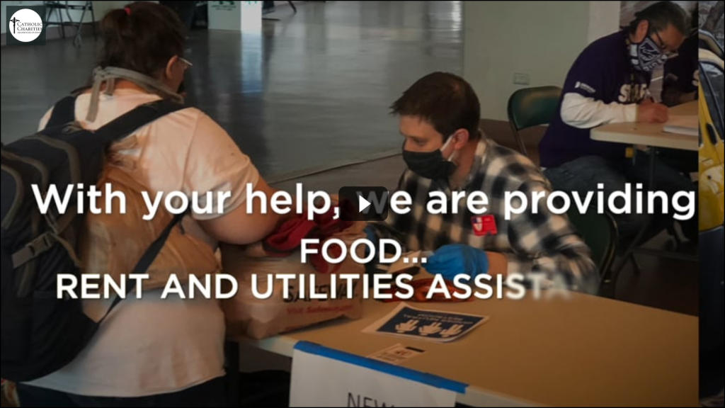 Screengrab of Catholic Charities of Denver's COVID-19 fundraising appeal video. The image shows their masked volunteers at work providing for those they serve.