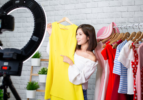 In this virtual event, a woman sells clothes on a livestream broadcast.