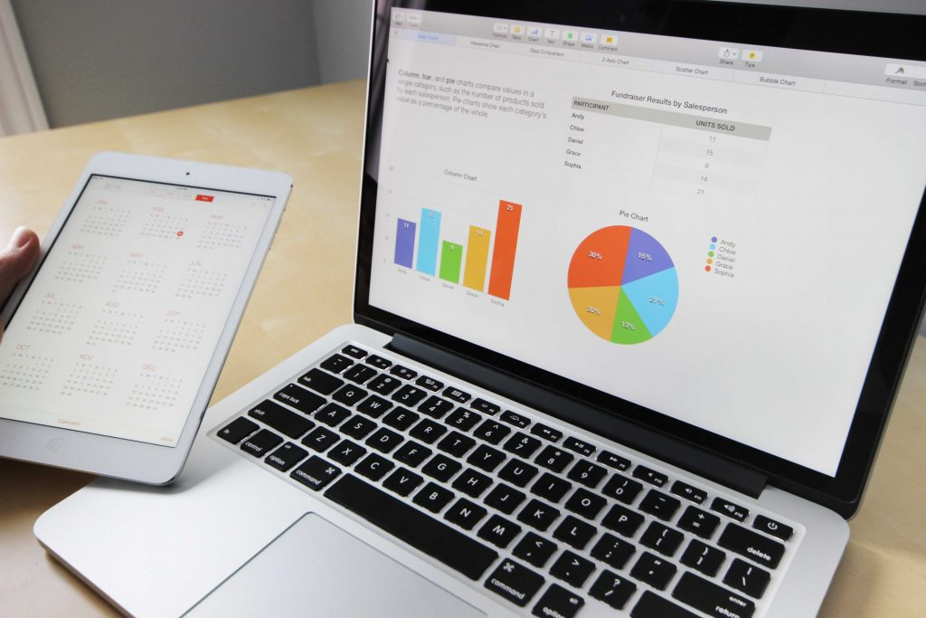Image of a bar graph and a pie graph on a laptop. A person's hand is visible next to the laptop holding a tablet with a calendar app on the screen.