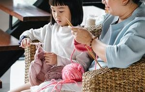 Little girl knitting with her mother