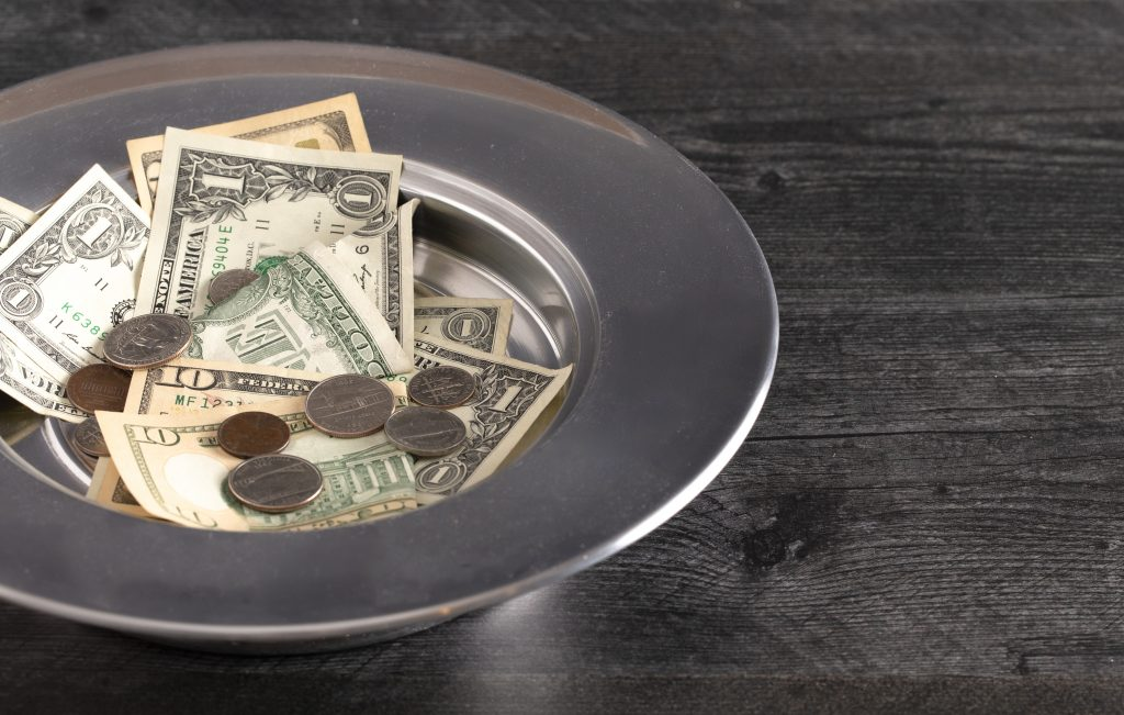 A silver collection plate filled with cash donations for a faith-based organization.