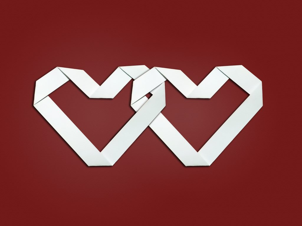 Two matching, interlinked white hearts on a red background.