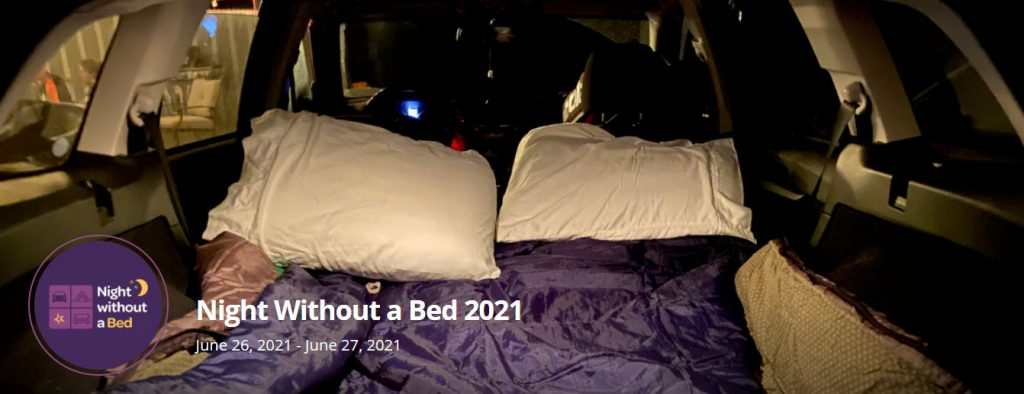 Cover image of the Night Without a Bed Challenge peer-to-peer event. It shows pillows and blankets in the back of someone's vehicle.