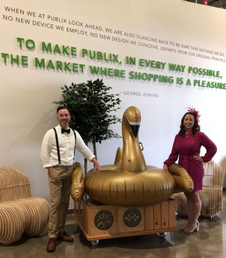Erin and Damian of Lakeland Volunteers In Medicine's Swan Before the Storm team posing with their golden, inflatable swan raft.