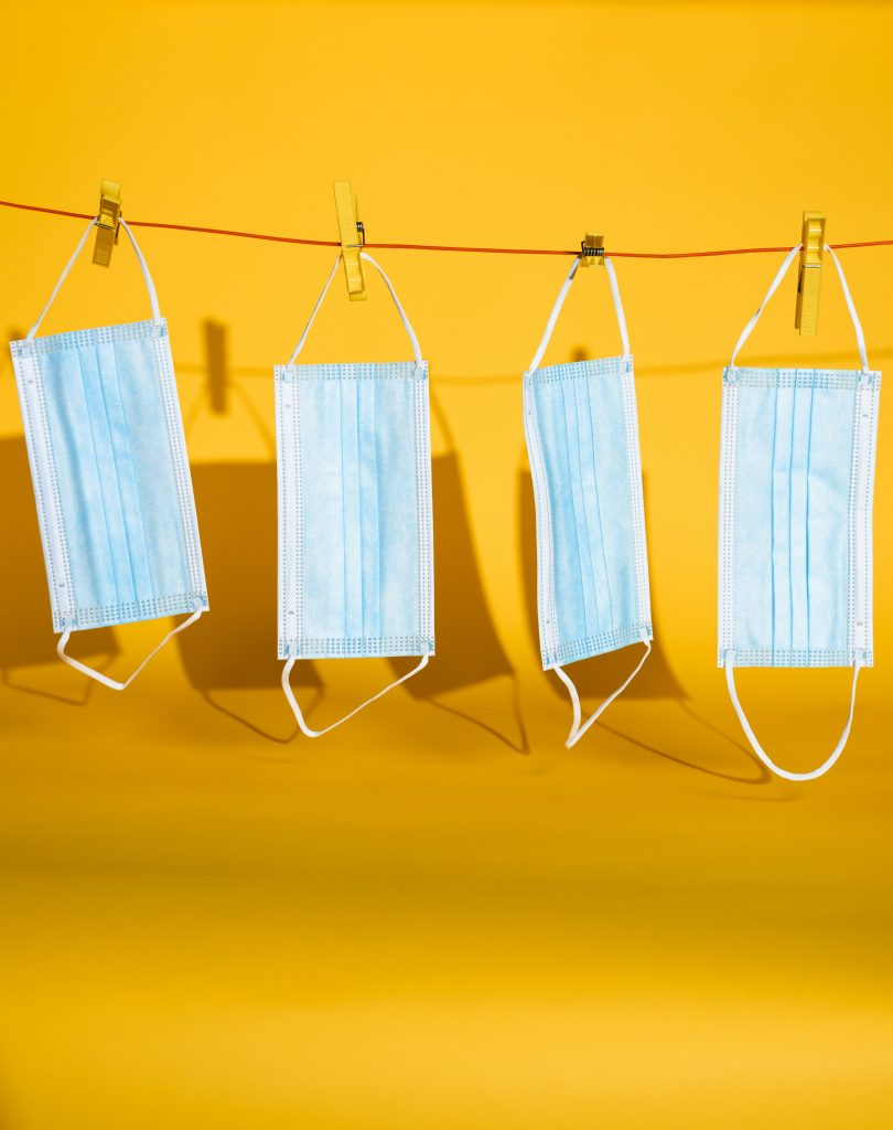Four disposable surgical masks hanging from a clothesline.